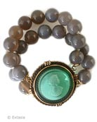 New from our Spring Collection, beautiful beaded Gray Agate bracelet with transparent Seafoam German glass intaglio center. Seafoam is a beautiful transparent mint green. Each bead is 1/2 inch in diameter. One size fits all, elastic band. This is a substantial piece. Metal and intaglio glass center piece is 1 3/4 inches in diameter. Bronze metal center. Each bracelet is hand made to order in USA