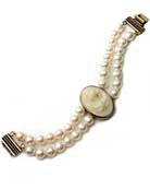 Our Ivory German glass cameo and pearl bracelet . We think this bracelet is beautiful and very flattering to any skintone. Image is from Greek mythology, of  Venus, often pictured with a dove, as seen here. One of our favorite cameos, it is 1 1/4 by 1 inch. Bracelet of genuine freshwater pearls measures 7 1/2 inches in length. Bronze.