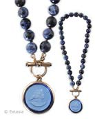 Toggle in front, 1 1/4 inch diameter pendant, on faceted hand knotted Sodalite beads.  18 inches in length. Shown here in our new transparent Saphhire German glass,  bronze metal. Each necklace made to order in the USA.