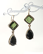 From our classic Kyros Collection, olivine German glass intaglio earring. Our popular drop earring measures 1 1/2 inches tall. Transparent olive intaglio top, opaque jet drop. French hook, bronze.